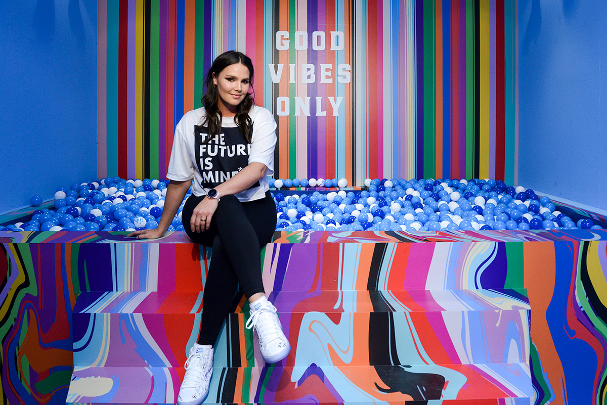 Candice Huffine sits beside ball pit at NYC pop up shop for new Fossil sport smartwatch