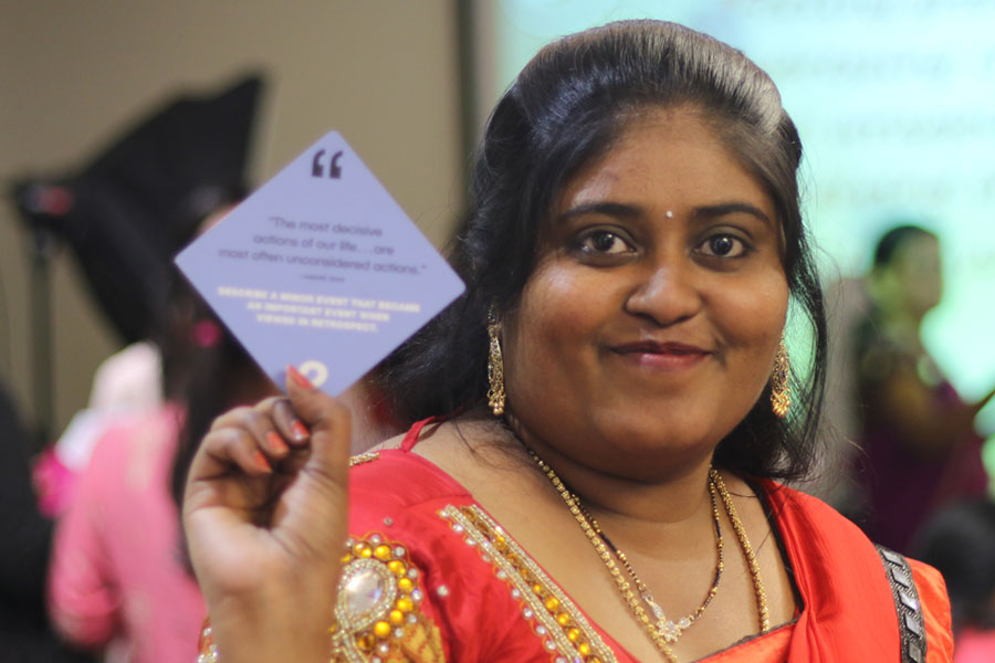 Fossil Group employee in India holds up card